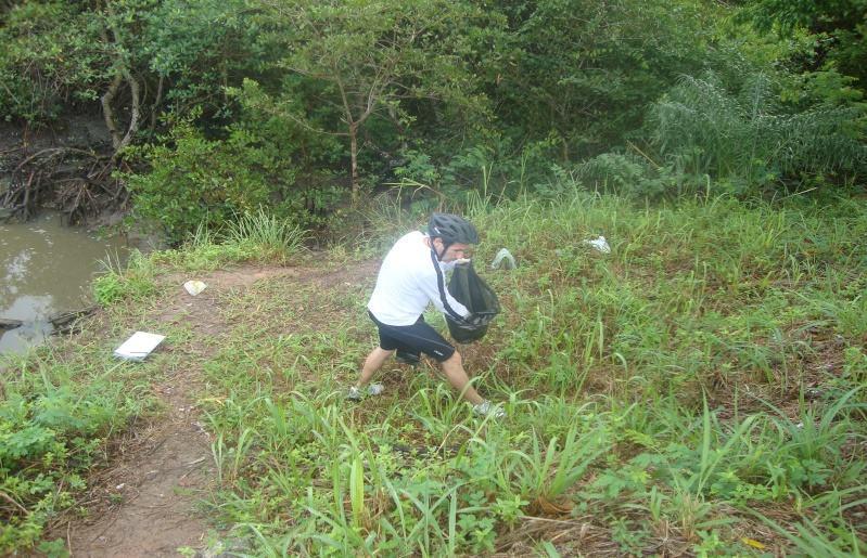Pesquisador recolhendo resíduos às margens do Rio dos Mangues.