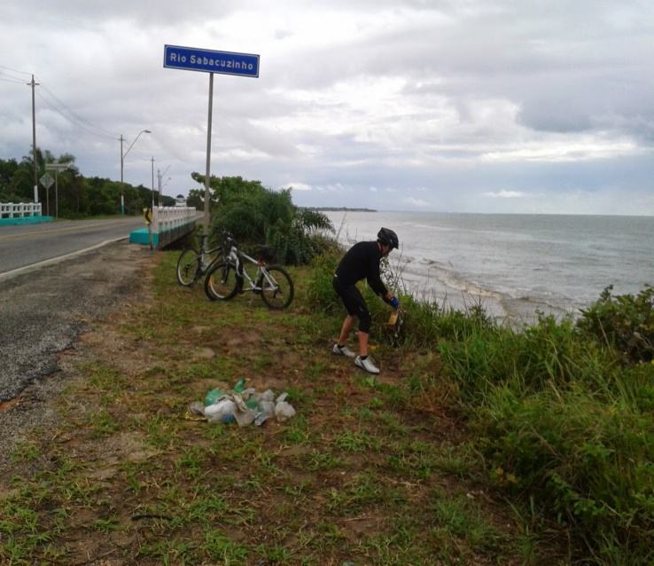Pesquisador retirando resíduos sólidos na desembocadura do Rio Sabacuzinho com a praia.