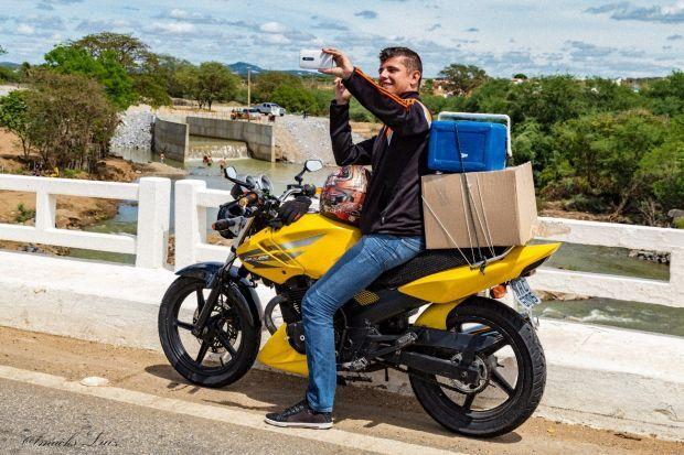Foto 7 – Moto Boy faz self sobre a ponte do Rio Paraíba em Monteiro – PB tendo como cenário o desembocar das águas da transposição no leito de aluvião do rio Paraíba.